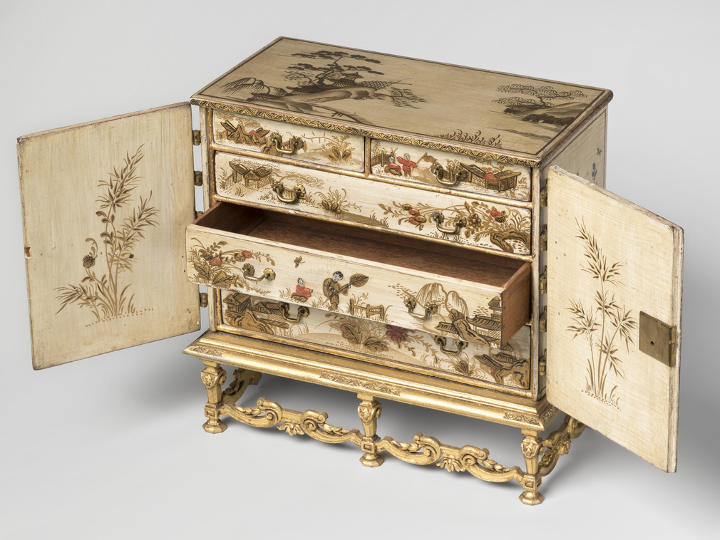 Miniature lacquered cabinet on stand. Cream ground, lacquered with oriental scenes, temple and figures in goldand red; top with mountainand buildings.Two front opening doors with brass hinges. Interior with two short overthree long