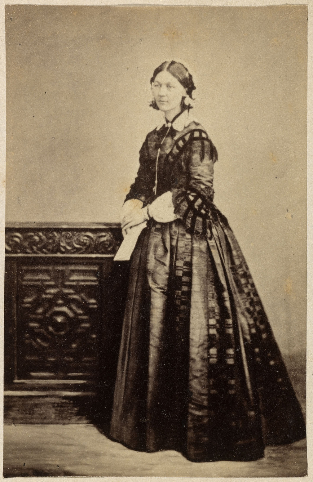 Carte-de-visite of Florence Nightingale standing facing partly left holding a letter. An engraved wooden chest stands to the left.<br /><br />Queen Victoria admired the work done by Florence Nightingale to improve nursing dur