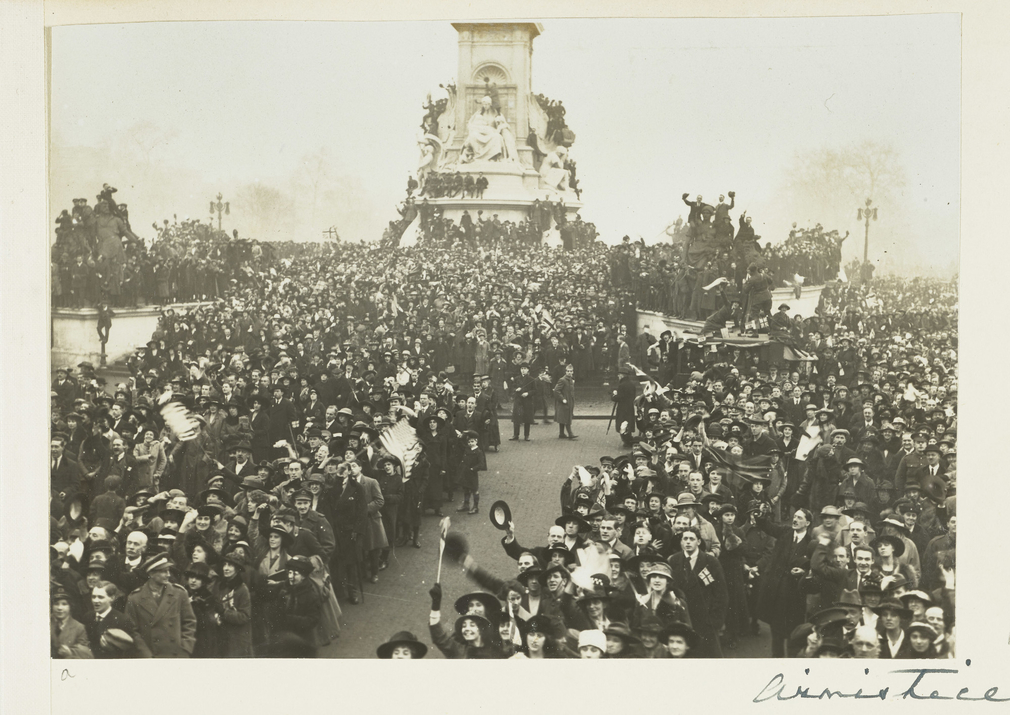 Photograph of a large crowd gathered outside of Buckingham Palace to celebrate the announcement of the end of World War I. The crowd stand around and sit on the Queen Victoria monument. Soldiers and civilians are shown cheering and waving flags.  Queen Ma