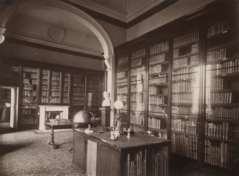 Photograph of the Prince Consort's Library, a room divided into two by an arch. The walls are lined with glazed bookcases, and there is a bookcase-library table in the centre. Beyond this is a globe and another table.
