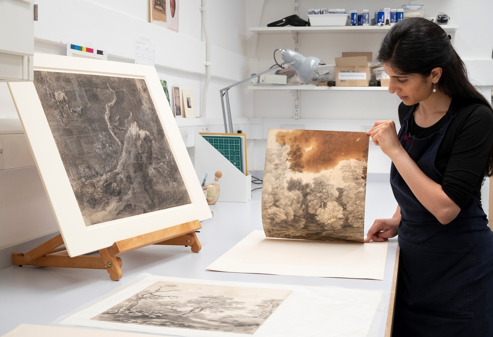 Paper Conservator Puneeta Sharma examines Thomas Gainsborough's Trees beside a lake, c.1748-50, which features a large oil stain from Gainsborough's studio