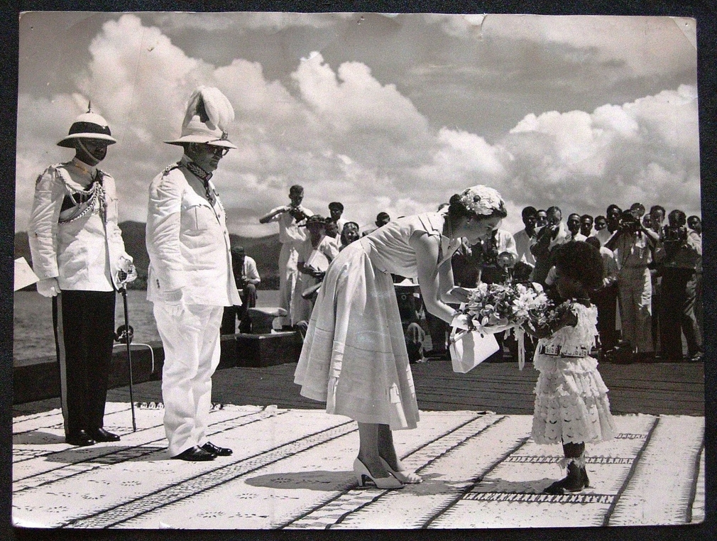 Photograph showing a Fijian child, Adi Kainona, presenting The Queen with a bouquet of Fijian flowers on The Queen's arrival at Suva Wharf from the SS Gothic. Behind the Queen stands Sir Ronald Garvey, Govenor of Fiji and another man in uniform. Photograp