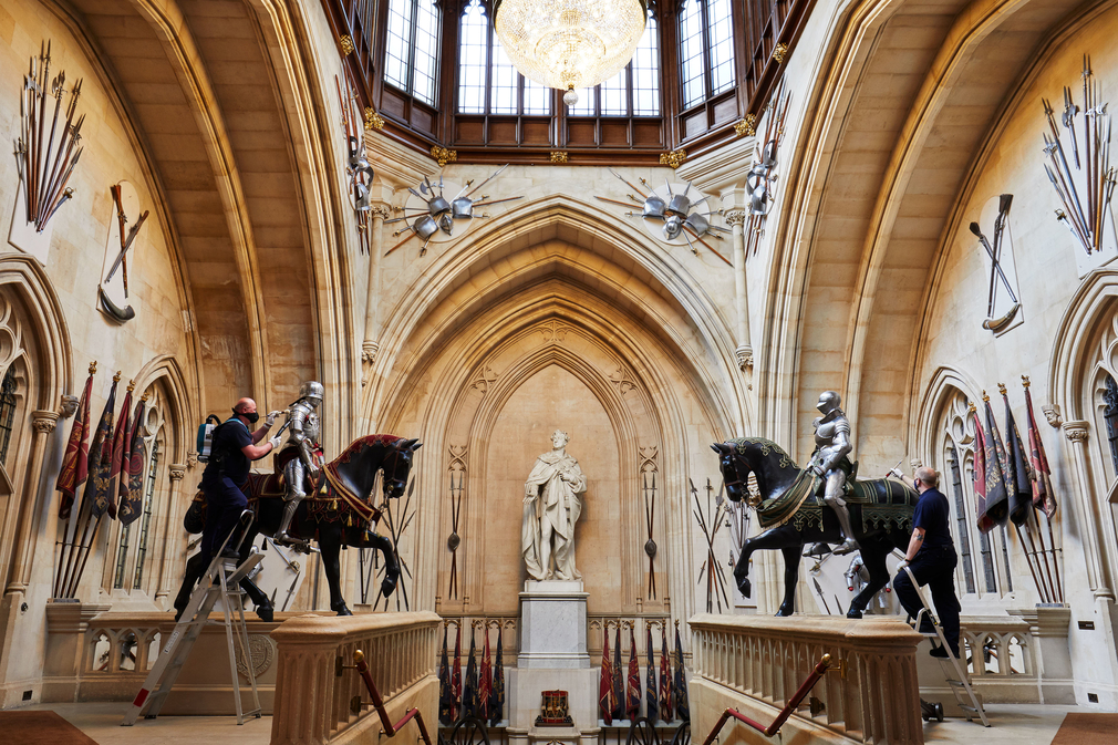 Members of staff dust the suits of armour that flank the Grand Staircase at Windsor Castle