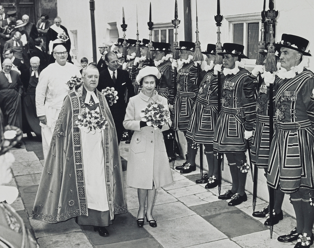 b/w. Queen and Dean of Westminster ; followed by Philip and other clergymen ; leaving Westminster Abbey after Maundy service, passing Guard of Honour of the Yeomen of the Guard.