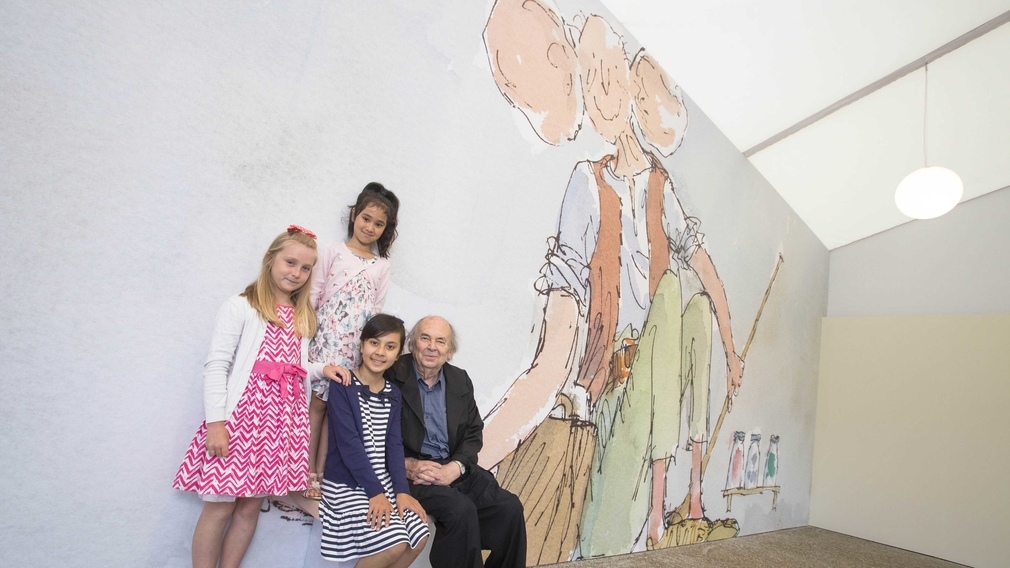 Sir Quentin Blake and children sitting on the hand of 'The BFG' at the Buckingham Palace Family Pavilion