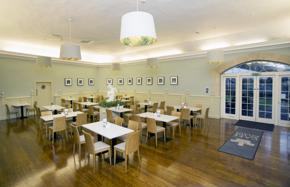 Polished wooden floors, wooden furniture and pale green walls in the Cafe