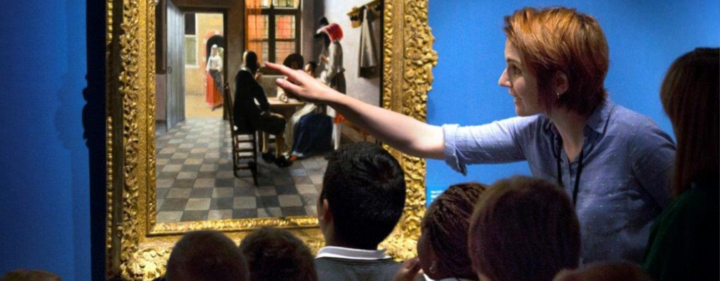 Group of school pupils and teacher looking closely at a painting on a gallery wall