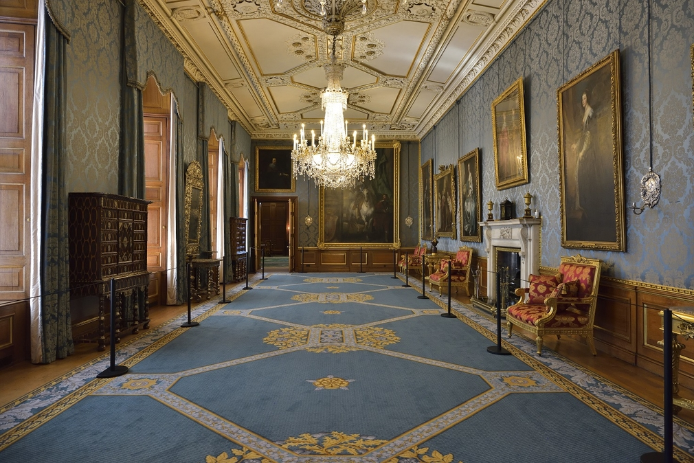 View of the Queen's Gallery with blue carpets, blue walls and grand paintings