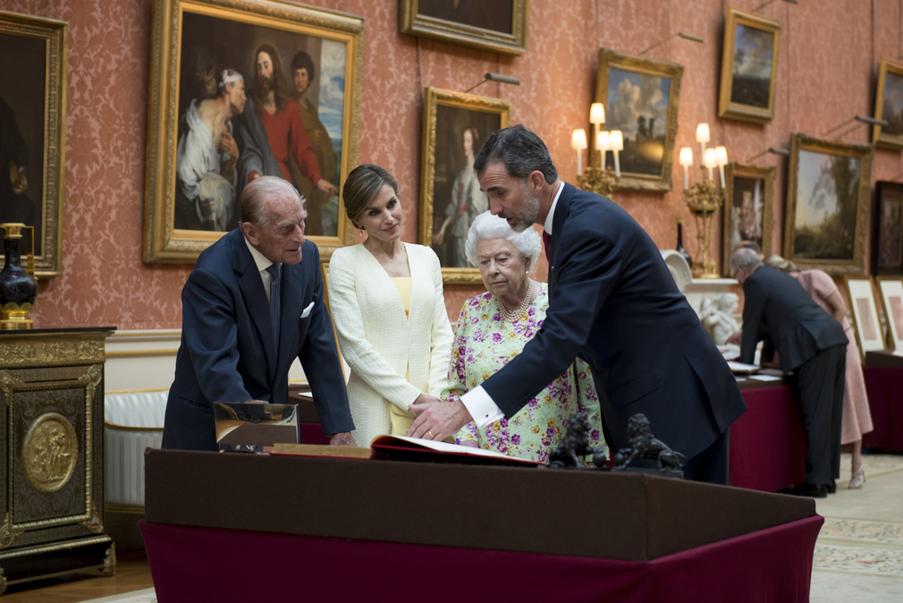 HM Queen Elizabeth and King Felipe view a table of archival items in the Picture Gallery of Buckingham Palace