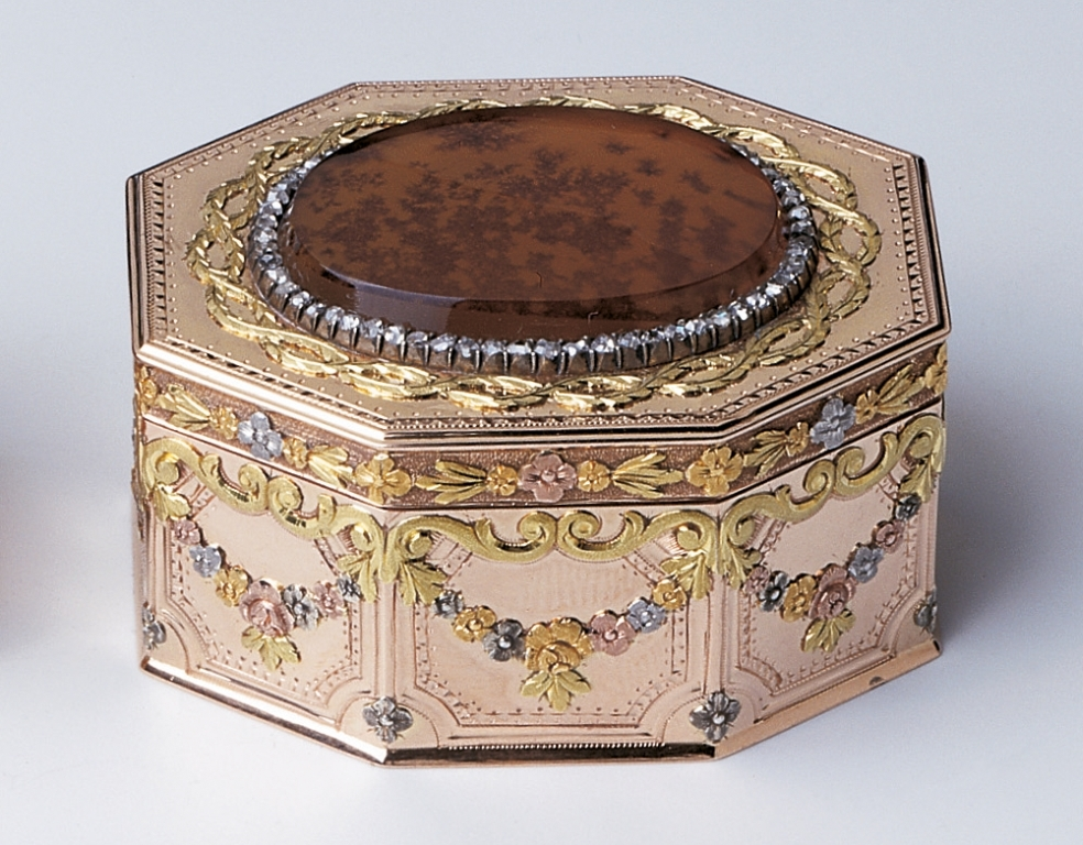 Patch box, octagonal, quatrecouleur gold with floral garlands and rococo scrolls on side panels, lid set with oval of moss agate, framed by rose diamonds and foliate twist. By including moss agate in mounted jewellery and boxes, Fabergé was continu