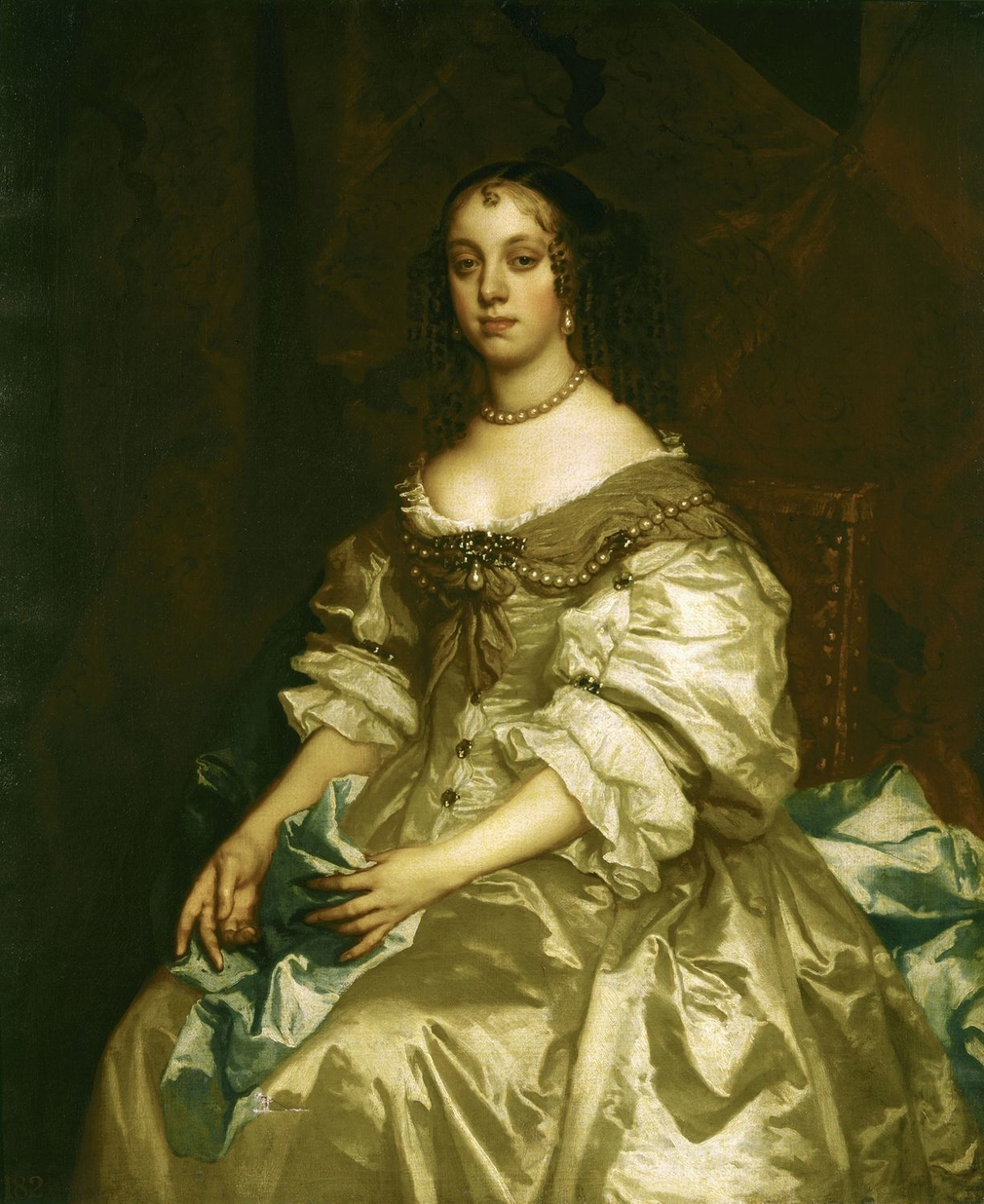 Catherine of Braganza (1638-1705) was the daughter of John IV of Portugal who became Charles II's Queen in 1662. This three-quarter-length portrait was painted, presumably for the sitter,soon after her arrival in England. It is the original for many