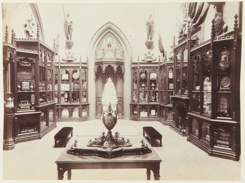Photograph of the Grand Vestibule with the new glazed Gothic showcases and fireplace, made in 1888 to display Queen Victoria's Golden Jubilee presents and loyal addresses; Queen Victoria's statue by JE Boehm under Gothic wooden canopy; displays of standar