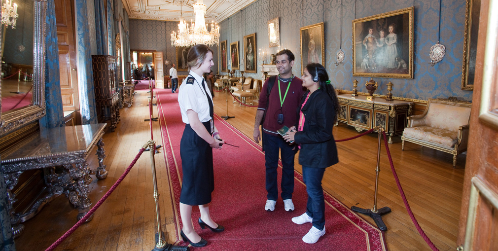A Warden with visitors in The Queen's Ballroom at Windsor Castle