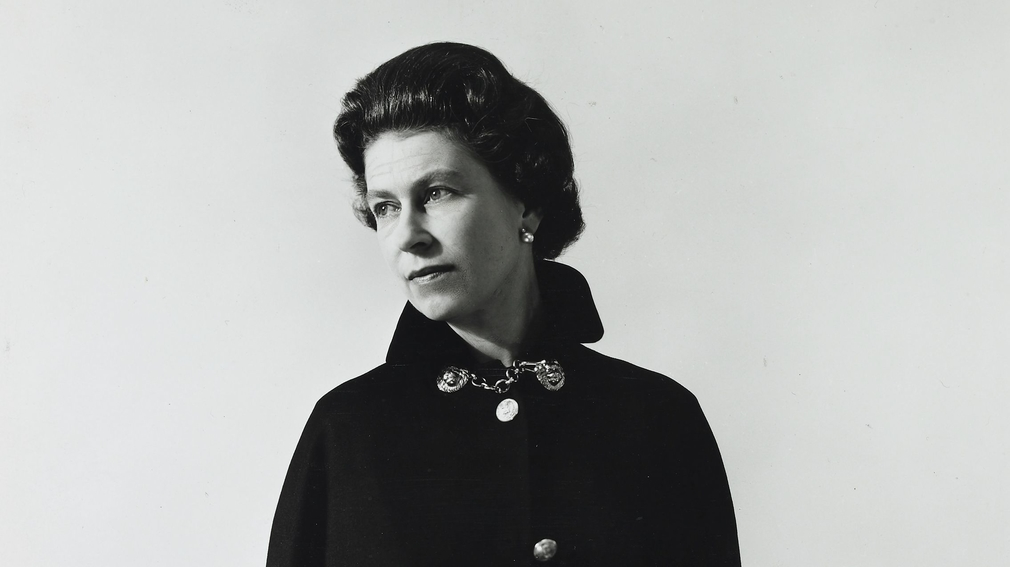 Portrait of The Queen wearing a drak Admiral's cloack against a plain background by the photographer Cecil Beaton in 1968.