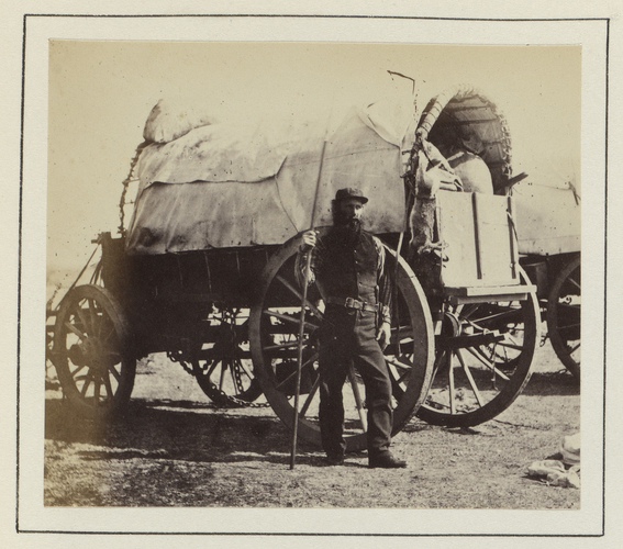 Man guarding a food supply waggon while encamped by a river in South Africa