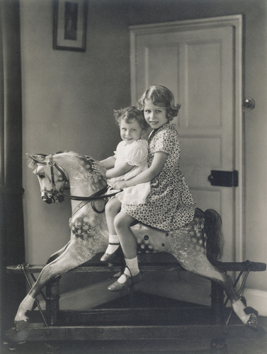 Princess Elizabeth and Princess Margaret riding a rocking horse at St Paul?s Walden Bury, August 1932