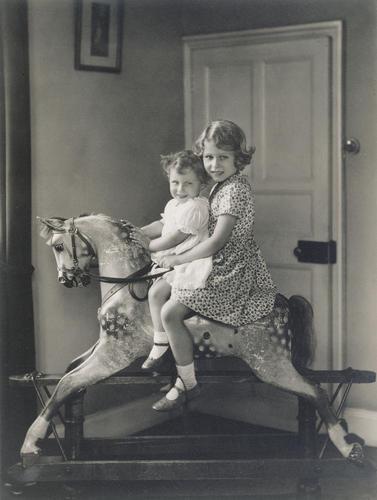 Princess Elizabeth and Princess Margaret riding a rocking horse at St Paul?s Walden Bury, August 1932