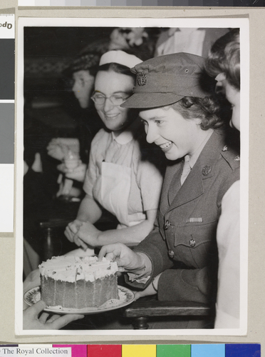 Princess Elizabeth accepting a piece of cake at a tea party at the Royal College of Nursing