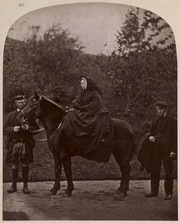 A photograph from the catalogue of Queen Victoria's Private Negatives, Vol. I.  Full length portrait of Queen Victoria seated on her pony Fyvie. On the left is John Brown, holding the pony's bridle. On the right is John Grant