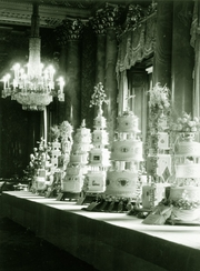 Photograph showing a table with a row of wedding cakes with various designs photographed on the occasion of HM Queen Elizabeth II's wedding in the Blue Drawing Room, Buckingham Palace. Floral arrangements by Edward Goodyear.