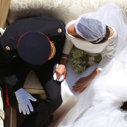 he Duke and Duchess of Sussex holding hands in the carriage following their wedding