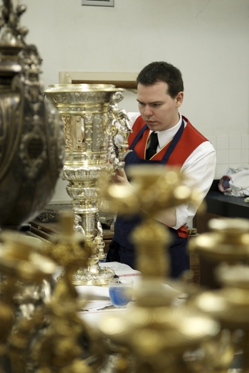 A footman polishing silver at Buckingham Palace