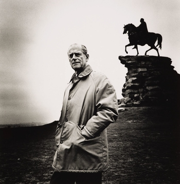 Photograph of the HRH The Duke of Edinburgh standing in front of the Copper Horse in the Great Park, Windsor. He faces the photographer.