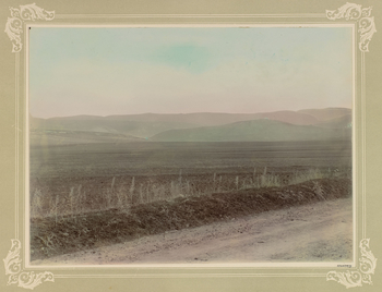 Photograph from a series showing Crimean battlefields, 1900-01. The photograph shows the field of Balaklava, which was the scene of the Charge of the Light Brigade. There is a path in the foreground with open land behind and hills in the distance. The pho