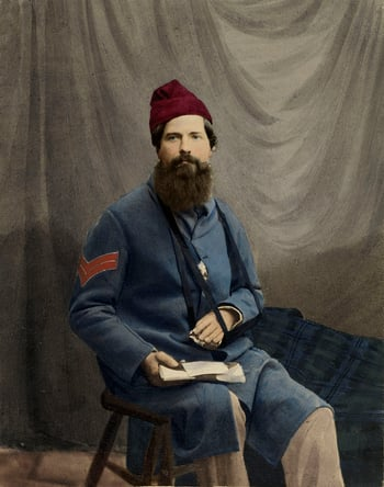 Hand-coloured photograph of Corporal Michael McMahon seated facing slightly right. He is wearing a blue military jacket and a red hat and his left arm is in a sling. There is a folded letter in his right hand. A sheet is draped behind him and there is a b
