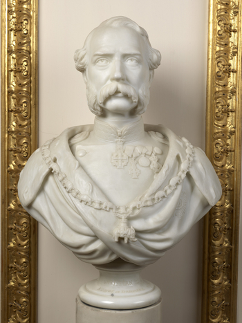 Marble bust of King Christian IX of Denmark; facing forwards; with drooping moustache and long sideburns; wearing a high-necked military jacket with medals and a cloak with the Collar of the Order of the Elephant.