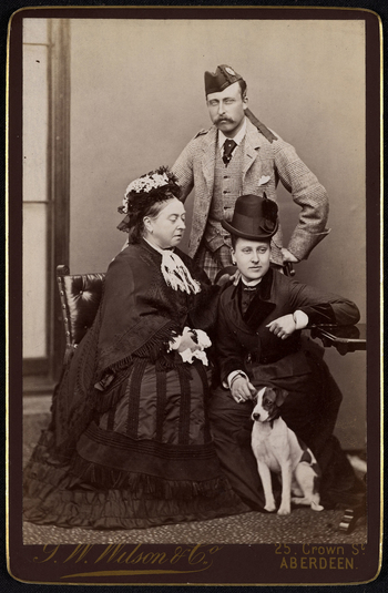 Portrait photograph of Queen Victoria (1819-1901) with Princess Beatrice (1857–1944) and Prince Arthur (1850-1942). The Queen and Princess Beatrice are seated. There is a terrier dog sitting in front of Princess Beatrice and Prince Arthur is standin