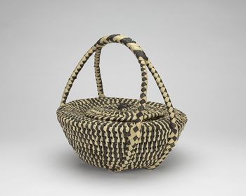 A black and white woven basket with a double handle, a removable round flat lid, and a half sphere-shaped body. This basket, with another (RCIN 74627), represents an industry which Queen Salote of Tonga, who presented them, had re-established on the islan