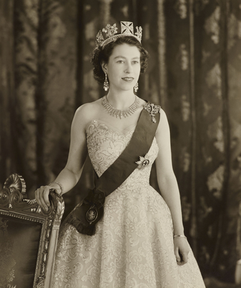 Three-quarter length photograph of HM Queen Elizabeth II (b.1926), standing and facing forwards with her head turned slightly to the right and her right hand resting on the back of a chair. HM The Queen is wearing a strapless dress with the Riband and Sta