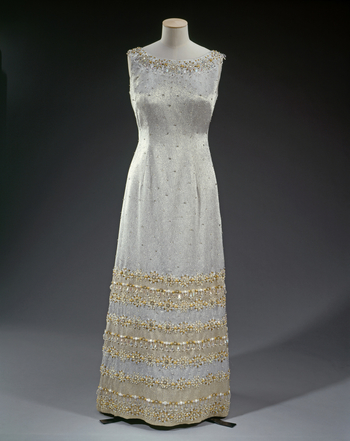 A sleeveless evening gown of silver lamé, embroidered with irredescent beading around the neckline and in deep panels around the hem.