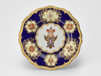 A Coalport porcelain dessert plate with a lobed gilt gadrooneed rim; dark blue border with six pale-yellow reserves painted with the Insignia of Russian Orders, surrounded by jewelled white dot borders; badge of Order of St. Andrew at centre.