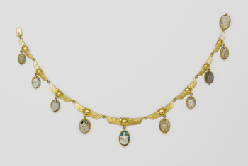 Gold necklace with ten ancient Egyptian steatite scarabs. The links, from which the scarabs are suspended, are formed by winged solar discs flanked, on either side, by rearing cobras. All scarabs are carved on the back and two are inscribed with the pren