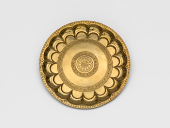 A gold plate with a sunken gadrooned rim stamped and chased with floral decoration. This plate is part of a courtly set of eleven items that was presented to Albert Edward, Prince of Wales during his four-month tour of India. When the Prince returned from