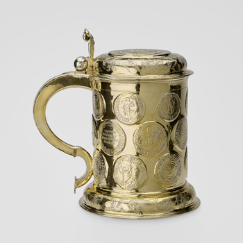 A German silver-gilt tankard, with hinged cover, inset with a medallion of Christ Triumphant, surrounded by inscriptions in French, German, Latin and Hebrew, and with a border of engraved flowers; with foliate thumbpiece and plain scroll handle; the cylin