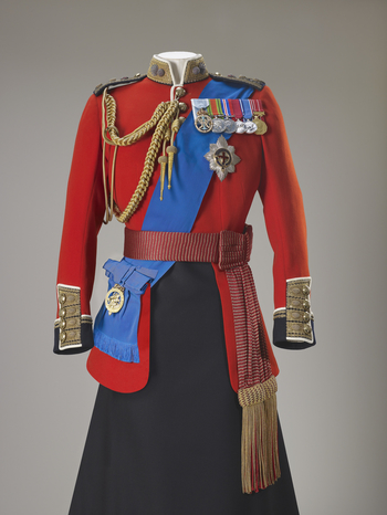 Colonel of the Grenadier Guards, full dress tunic, tailored for The Queen. Scarlet wool with a mandarin-style collar with gold braid; evenly spaced brass buttons and white piping down centre front; four brass buttons on gold braid over blue cuffs.<br /><b