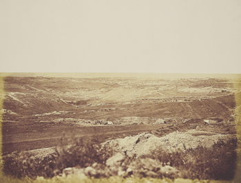 Photograph of a ravine in the Crimea named by Robertson as the Valley of the Shadow of Death. A trench runs the breadth of the photograph, with several piles of cannonballs to the right. A town can be seen in the distance, possibly Sevastopol or Balaklava