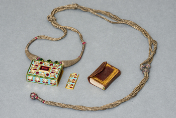 An amulet or taviz necklace formed of a rectangular box of turquoise enamelled gold inlaid with diamonds and rubies, and enamelled dark and light green on the back. The side of case slides to reveal a leather bound miniature Quran manuscript (RCIN 1146163