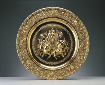 A large silver gilt sideboard dish with a relief of the Triumph of Bacchus and Ariadne, who stand in a chariot, surrounded by celebrating centaurs, within a wreath of ivy leaves; the border is chased with Bacchic masks, trophies and fruiting vines on a tr