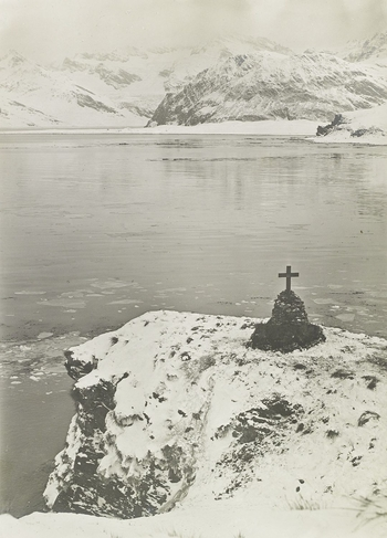 Photograph of a Cairn in the form of a cross on a pile of stones on the headland at the entrance to Gritviken Harbour, South Georgia.  Wilkins joined Quest as an ornithologist, but he also documented the expedition with his photographs, covering the voy