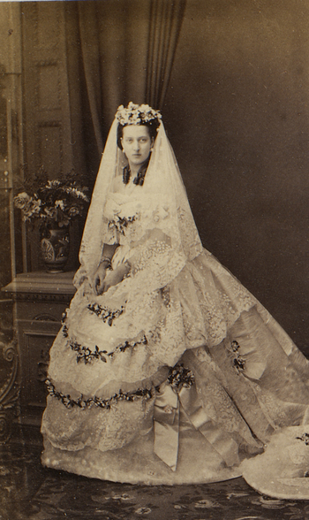 Full length formal photographic portrait of Alexandra, Princess of Wales standing, wearing her wedding dress. She faces the viewer and wears a floral decoration in her hair. Vase of flowers in left background.