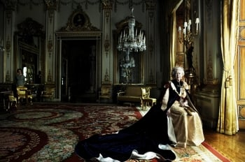Photograph of HM Queen Elizabeth II seated in full length facing the viewer in the White Drawing Room of Buckingham Palace. The Queen is illuminated by light from the window on her left and she wears Garter robes and a diamond tiara. A