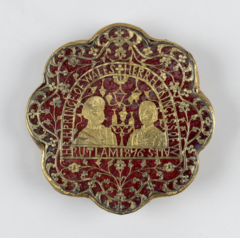 A scallop-edged brooch of red glass with pierced sheet gold depicting two portraits, supposedly the Prince and Princess of Wales. The portraits are bordered with a dedication to the Prince and Princess and a foliate border.