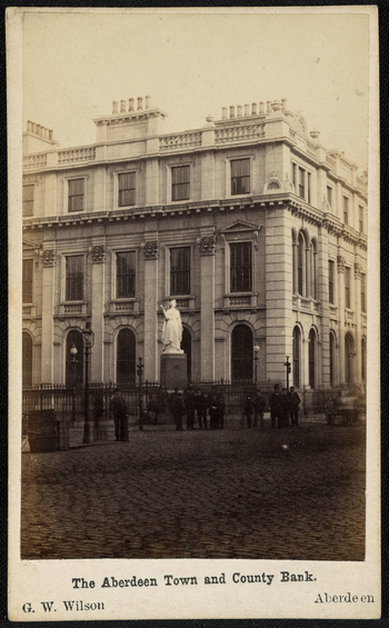 Photograph showing a large building standing standing at the intersection of St Nicholas and Union Streets in Aberdeen. The building features Corinthian columns and three floors. Outside the building stands a statue of Queen Victoria that was sc