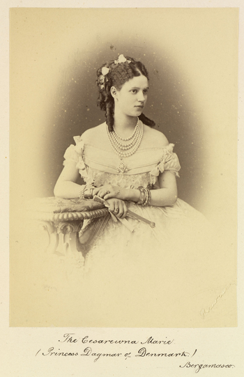 Half-length photograph of Tsesarevna Maria Feodorovna, later Empress of Russia. She is sitting with her head turned to the right and her right arm resting on the table beside her. She is wearing a number of pieces of jewellery including five strings of pe