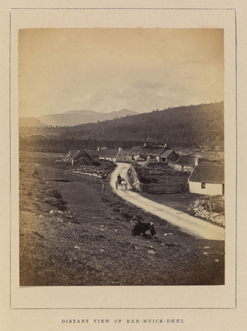 Photograph of a single track road leading diagonally through the frame with small cottages to the side. A man is seated on the ground in right side profile, with his left hand resting on his left knee. In thebackground is Ben Macdui.  Ben Macdui sta