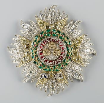 Order of the Bath star. Eight-pointed diamond set silver star with flaming rays overlaid with eight-pointed cross of yellow diamonds in gold; the centre has three gold crowns on diamonds, encircled by motto TRIA JUNCTA IN UNO of diamonds on red enamel, su